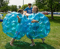 "Katelyn Pinter and ""Wish Kid"" Charlotte Larochelle try a little Sumo Bubble Wrestling with ""Wish Kid"" Eric Adams as referree during the Make A Wish event at Hesky Park on Saturday afternoon.  (Karen Bobotas/for the Laconia Daily Sun)"