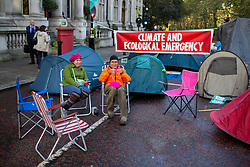© Licensed to London News Pictures. 08/10/2019. London, UK. An Extinction Rebellion protester knits at a roadblock near St James's Park . Photo credit: George Cracknell Wright/LNP