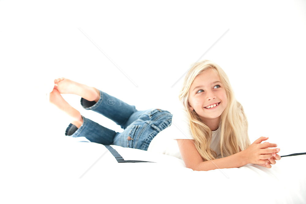 little blonde girl smiling and looking off while resting on a bed