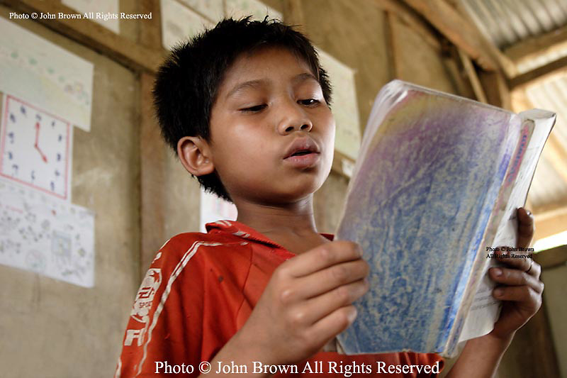 A student reads aloud from his Lao language textbook during a class at Ban Buamlao Primary School in Ban Buamlao, Laos.