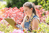 Female supervisor writing on clipboard in garden