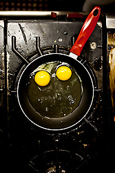 Two Raw Eggs being cooked in a pan with red handle.