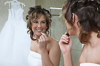 Bride applying lipstick in mirror