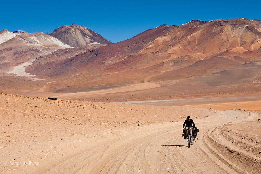 A cyclist travel the remote Sud Lipez region in south-western Bolivia, which averages 15,000' asl and is full of volcanoes and high-altitude multi-colored lagoons throughout this Spectacular Andean mountain range.