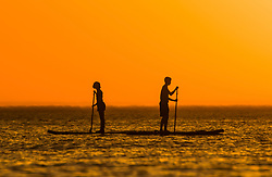 © Licensed to London News Pictures. 02/07/2018. Aberystwyth, UK. Two addle boarders at sunset in Aberystwyth at the end of yet another hot and cloudless day, as the prolonged heatwave continues to dominate the weather over the UK. Photo credit: Keith Morris/LNP
