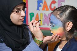 Teacher painting the face of a pupil at the Nottingham Islamia school Aid Fair,