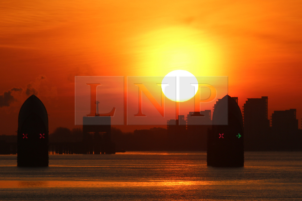 © Licensed to London News Pictures. 25/03/2017. Sunrise over the Thames Barrier this morning as viewed from Greenwich on the last day of Greenwich Mean Time before the UK moves to British Summer Time this evening. Credit : Rob Powell/LNP