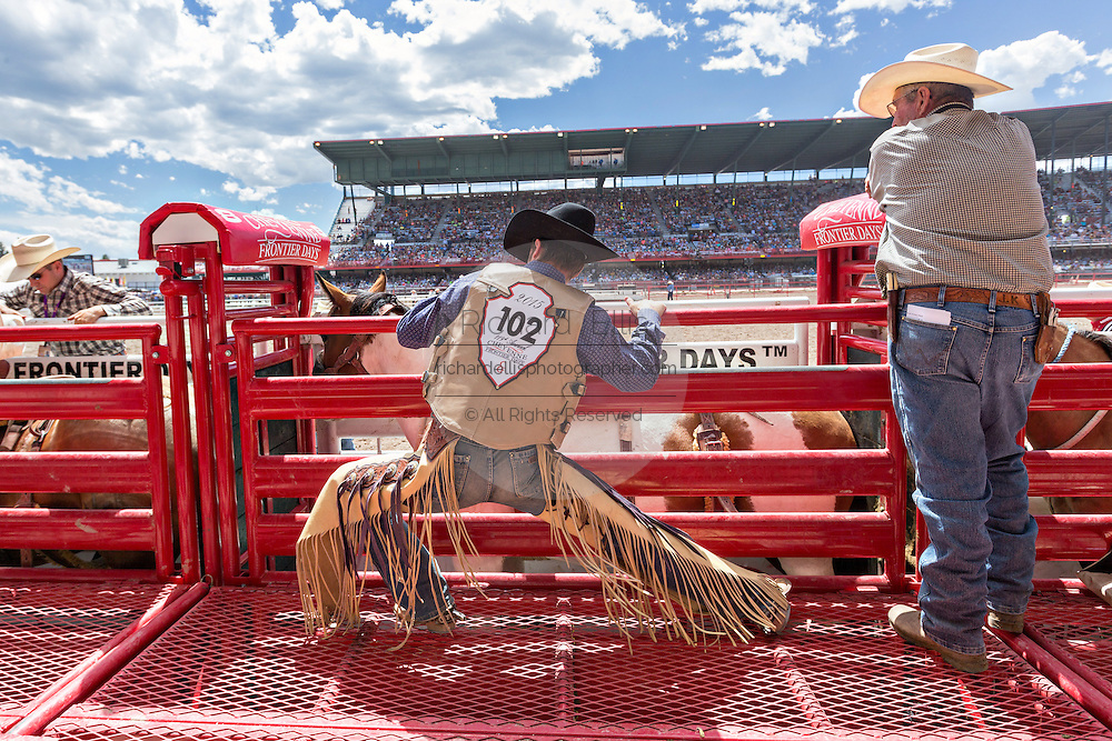 A rodeo rider stretches before climbing onto a bucking bronco during the Cheyenne Frontier Days rodeo July 25, 2015 in Cheyenne, Wyoming. Frontier Days celebrates the cowboy traditions of the west with a rodeo, parade and fair.