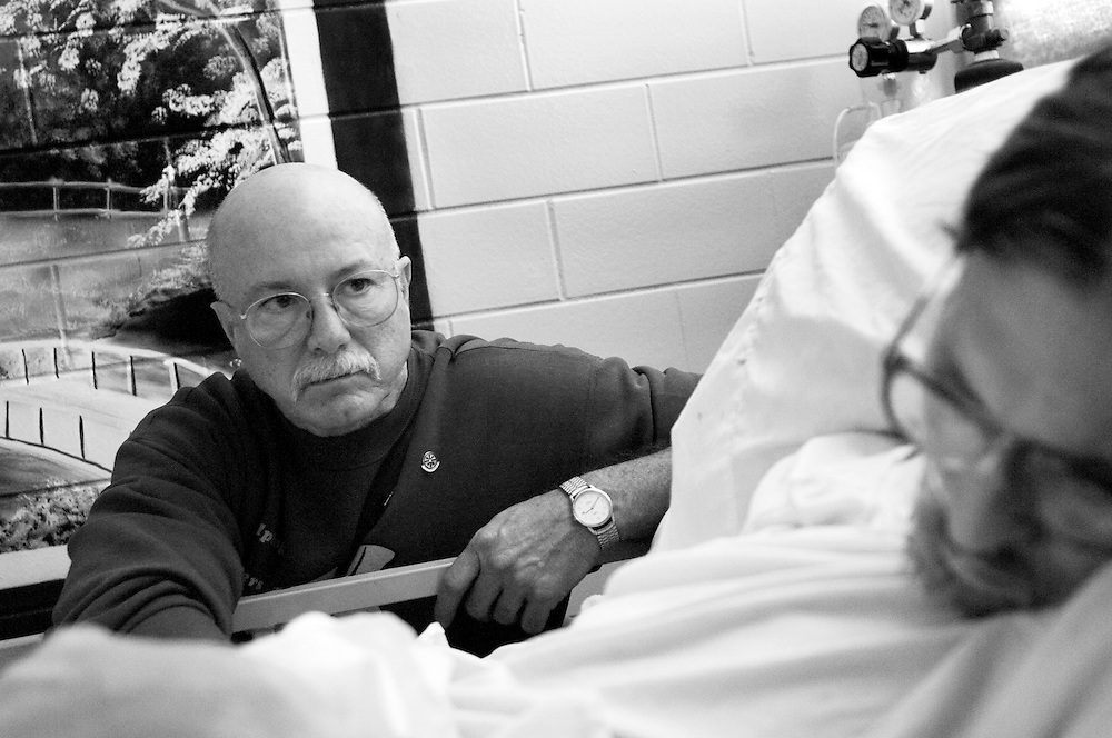 """Richard """"Grasshopper"""" Liggett, 55, who is fighting advanced liver and lung cancers, slips off to sleep under the watchful eye of prison hospice volunteer Randolph Matthieu. One of the most important aspects of the Angola State Penitentiary Hospice program is that dying patients are never left alone during their last days."""
