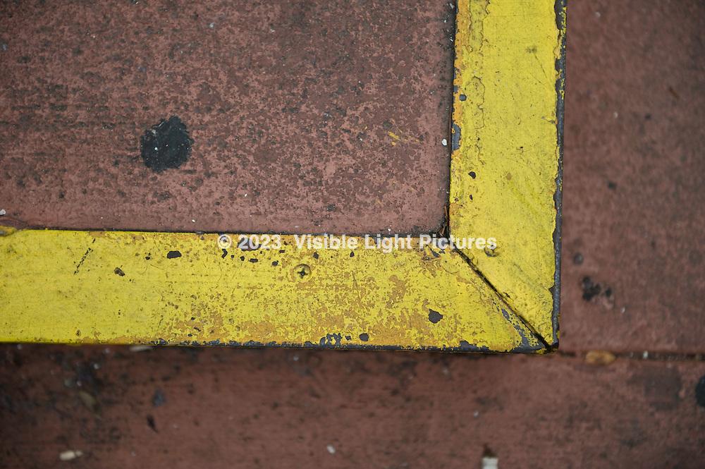 Yellow painted metal edge on a brown sidewalk step.