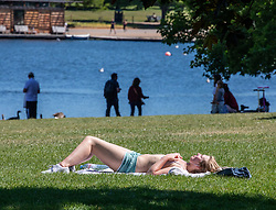 © Licensed to London News Pictures. 19/05/2020. London, UK. A women sunbaths along the Serpentine in the warm sunshine in Hyde Park as weather experts predict a high of 27c this week. Last week the Government eased the law on lockdown to let people spend more time outside. Photo credit: Alex Lentati/LNP