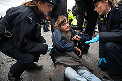 © Licensed to London News Pictures. 15/03/2019. London, UK. Emma a student is arrested by police on Westminster Bridge.  School children across the UK took part in an international day of action protesting inaction over climate change. An 'after party' was held on Westminster Bridge, blocking traffic for several hours.  Photo credit: Guilhem Baker/LNP