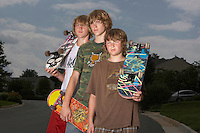 Three teenage brothers (13-17) standing on street holding skateboards portrait