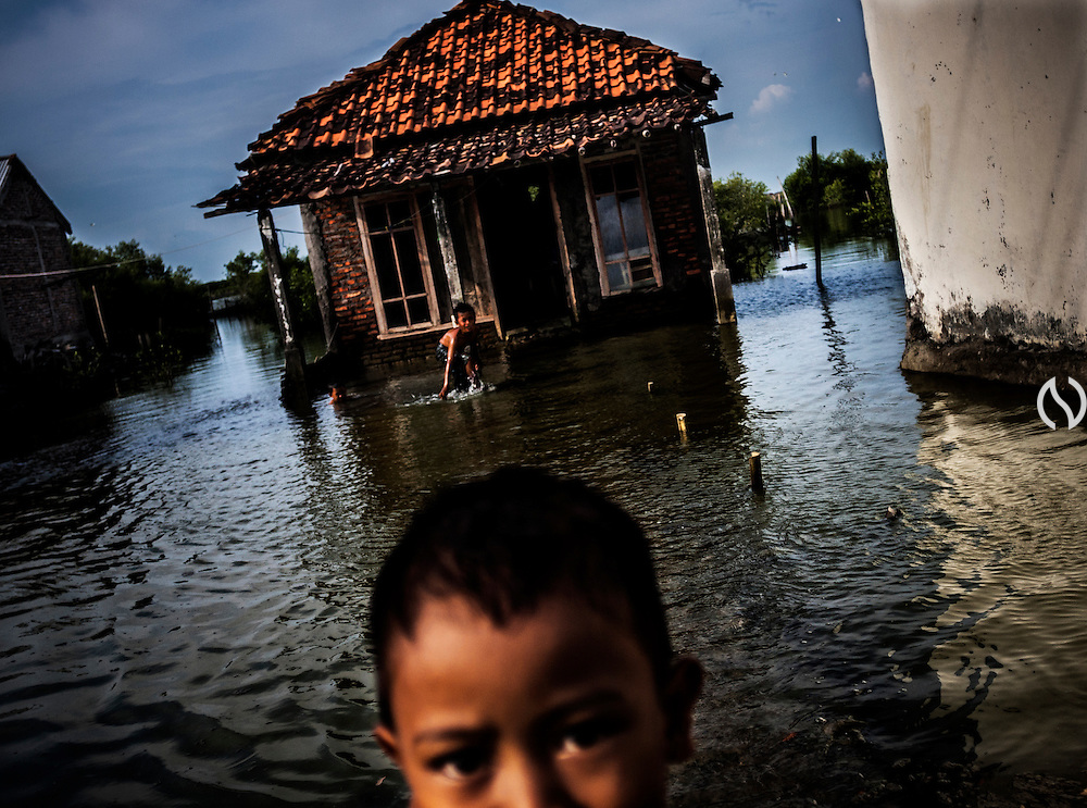 Children play at the frequently flooded front yard of a house in Bedono village, near Semarang.