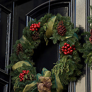 Christmas Wreath with decorations on front door in Greenwich Village.<br /> <br /> The tradition of hanging wreath during Christmas is essentially a Christian ritual. This is done during the Christmas season, traditionally used to prepare for the coming of Christ, also known as the Advent season in Christianity. Traditionally, the Christmas wreaths were made of evergreen leaves, which are still symbolize the permanence of life. A traditional wreath is a circle, which means that there is no beginning or end and that God is eternal.