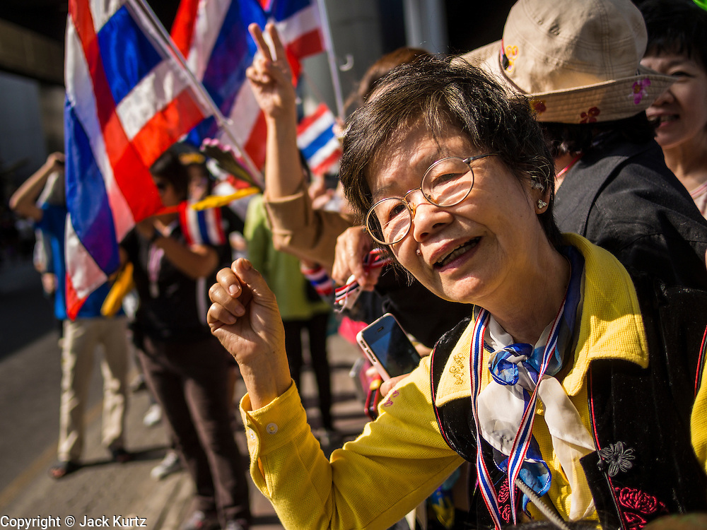 22 DECEMBER 2013 - BANGKOK, THAILAND: Anti-government protestors in the Asok intersection of Bangkok. Hundreds of thousands of Thais gathered in Bangkok Sunday in a series of protests against the caretaker government of Yingluck Shinawatra. The protests are a continuation of protests that started in early November and have caused the dissolution of the Pheu Thai led government of Yingluck Shinawatra. Protestors congregated at home of Yingluck and launched a series of motorcades that effectively gridlocked the city. Yingluck was not home when protestors picketed her home.     PHOTO BY JACK KURTZ