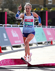 Charlotte Purdue crosses the finish line to win the women's race during the Vitality Big Half in London.