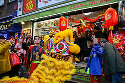 © Licensed to London News Pictures. 25/01/2020. London, UK. Chinese lion dancers visits businesses in London's China Town during as Chinese and non-Chinese community celebrates Chinese New Year, the Year of the Rat. Photo credit: Dinendra Haria/LNP