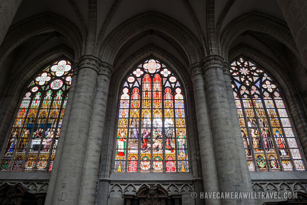 Three stained glass windows at the Cathedral of St. Michael and St. Gudula (in French, Co-Cathédrale collégiale des Ss-Michel et Gudule). A church was founded on this site in the 11th century but the current building dates to the 13th to 15th centuries. The Roman Catholic cathedral is the venue for many state functions such as coronations, royal weddings, and state funerals. It has two patron saints, St Michael and St Gudula, both of whom are also the patron saints of Brussels.