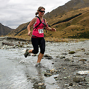 Runner Sarah Liddell crosses Moke Creek on the Ben Lomond High Country Station during the Pure South Shotover Moonlight Mountain Marathon and trail runs. Moke Lake, Queenstown, New Zealand. 4th February 2012. Photo Tim Clayton