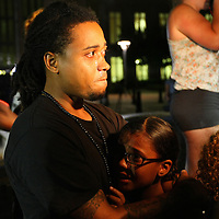 A man and child react to the not guilty verdict in the George Zimmerman murder trial at the Seminole County Courthouse on Saturday, July 13, 2013, in Sanford, Florida.  Zimmerman had been charged for the 2012 shooting death of Trayvon Martin and was found not guilty by a jury of six women. The protests on the grounds ended peacefully after the verdict was read. (AP Photo/Alex Menendez)