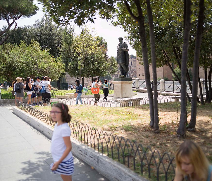 turisti si fotografano davanti all'Imperatore cesare augusto sui fori imperiali Roma,<br /> <br /> Tourists photographing in front of the emperor Caesar Augustus the Imperial Forum in Rome,