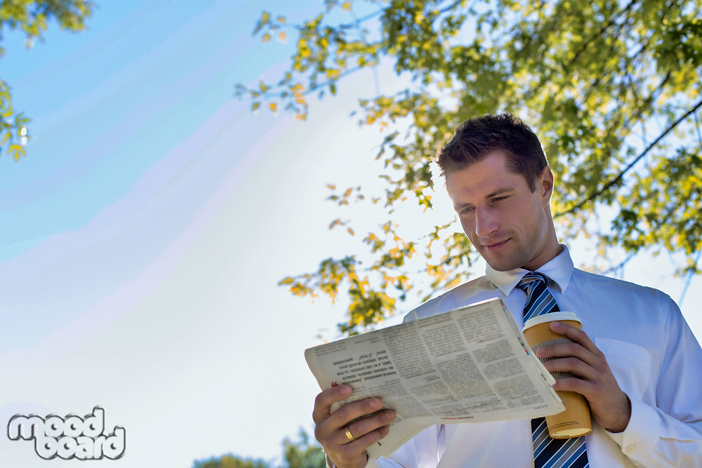Portrait of handsome mature businessman holding cup of coffee while reading newspaper in park during break