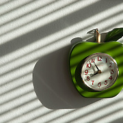 Apple-shaped clock with interesting shadows from a window