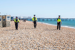 © Licensed to London News Pictures.05/04/2020. Brighton, UK. Members of the police can be seen patrolling the beach and talking to the public advising them that they can not sit down and have to keep moving in Brighton and Hove. Photo credit: Hugo Michiels/LNP