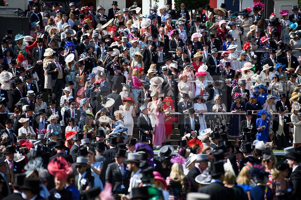 © Licensed to London News Pictures. 21/06/2018. London, UK. Racegoers in the Royal Eclosure watch over the parade ring at Ladies Day at Royal Ascot at Ascot racecourse in Berkshire, on June 21, 2018. The 5 day showcase event, which is one of the highlights of the racing calendar, has been held at the famous Berkshire course since 1711 and tradition is a hallmark of the meeting. Top hats and tails remain compulsory in parts of the course. Photo credit: Ben Cawthra/LNP