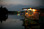 As the sun sets, people gather to catch the evening breeze on the front porch of the houseboat Marial on Dal Lake.