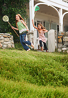 Two girls (7-9 10-12) holding fishing nets running in front of house