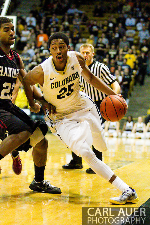 November 24th, 2013:  Colorado Buffaloes junior guard Spencer Dinwiddie (25) drives the ball past Harvard Crimson junior guard/forward Wesley Saunders (23) in the second half of action in the NCAA Basketball game between the Harvard Crimson and the University of Colorado Buffaloes at the Coors Events Center in Boulder, Colorado