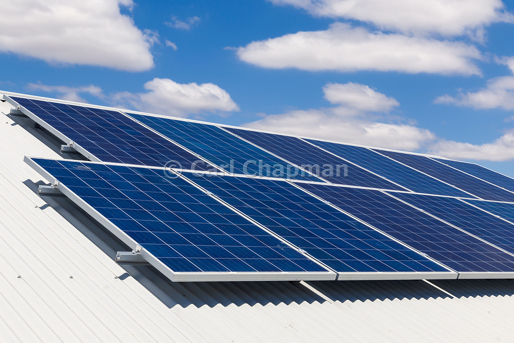 Solar electricity panels on corrugated tin roof under blue sky and cloud, providing green energy electric power. <br />