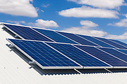 Solar electricity panels on corrugated tin roof under blue sky and cloud, providing green energy electric power. <br /> <br /> Editions:- Open Edition Print / Stock Image