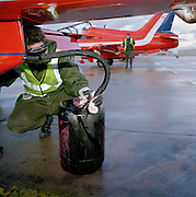Ground crew prepares dye derv mixture for red, white, blue smoke for 'Red Arrows', Royal Air Force aerobatic team Hawk jet.