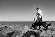 A man walks his dog along the jetty Saturday July 2, 2016 at Higbee Beach in Cape May, New Jersey. Photo by William Thomas Cain/Cain Images