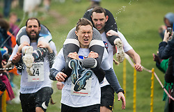 © Licensed to London News Pictures. 08/04/2018. Dorking, UK. Water being thrown on competitors as they take part in the 2018 annual Wife Carrying Race in Dorking, Surrey. The race, which is run over a course of 380m, with both men and women carry a 'wife' over obstacles, is believed to have originated in the UK over twelve centuries ago when Viking raiders rampaged into the northeast coast of England carrying off any unwilling local women . Photo credit: Ben Cawthra/LNP