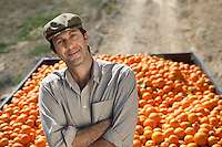 Portrait of farmer leaning on trailer with oranges