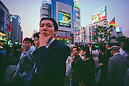 At close of work, young Tokyo residents converge on a busy Tokyo intersection in Shinjuku at dusk.