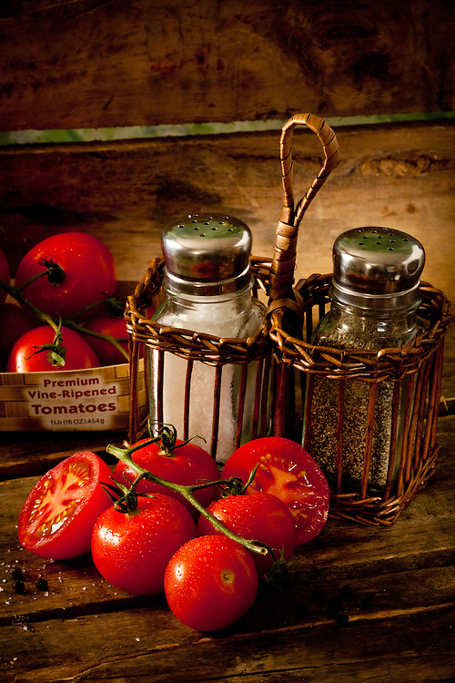 Tomatoes on wooden crate green mottled background,salt and pepper shakers