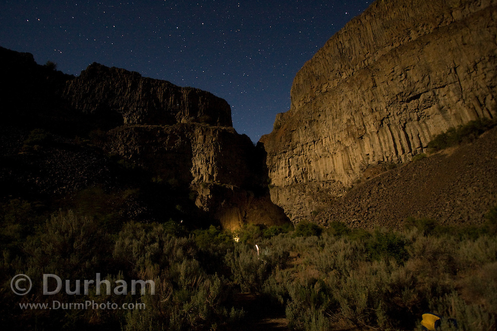 The lights used by biologists create a glow against basalt cliffs while they work late into the night during a noctrunal bat survey at The Nature Conservancy's Dutch Henry Falls preserve in central Washington.