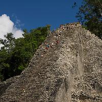 Tourists climb a the Nohoch Mul pyramid at the Mayan ruins at Coba.