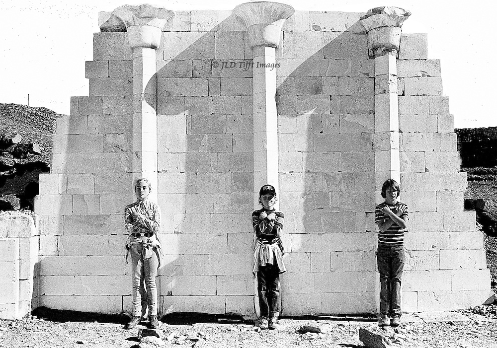 Three children aged 10-13 assume Pharaonic poses with crossed arms, standing in front of the reconstructed. pilastered wall, Saqqara.