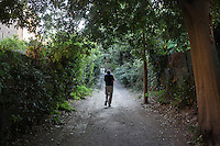 ROME, ITALY - 27 AUGUST 2016: A homeless man hosted at the accommodation center ran the Sisters of the Missionaries of Charity, the religious congregation founded by Mother Teresa in 1950, walks along the alley at San Gregorio al Celio in Rome, Italy, on August 27th 2016.<br /> <br /> Mother Teresa, also known as Blessed Teresa of Calcutta, was an Albanian Roman Catholic nun and missionary. She founded the Missionaries of Charity, a Roman Catholic religious congregation, whose members must adhere to the vows of chastity, poverty, and obedience, as well as the vow to give wholehearted free service to the poorest of the poor. Shortly after she died in 1997, Pope John Paul II waived the usual five-year waiting period and allowed the opening of the process to declare her sainthood. She was beatified in 2003. A second miracle was credited to her intercession by Pope Francis, in December 2015, paving the way for her to be recognised as a saint by the Roman Catholic Church. Her canonisation is scheduled for September 4th 2016, a day before the 19th anniversary of her death.