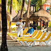 Resort worker is sweeping sand off the beach chairs in Cozumel, Mexico.