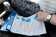 A middle-aged lady reads through instructions from the driver's seat of her car during a self-administered Coronavirus (COVID-19) test in south London. There are four steps to the self-administered Covid-19 test (inserting a swab into the nose and throat) which the public works through in their car, windows up and all communications with army personnel via phone, in a south London leisure centre, on 2nd June 2020, in London, England. The kit provided consists of a booklet, plastic bag, swab, vial, bar codes and a sealable biohazard bag. The swab sample is taken from the back of the throat and nasal passage with the contents sealed and returned to soldiers through a narrow window. The whole process takes between 5-10mins with results available with 48hrs.
