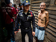 03 SEPTEMBER 2016 - BANGKOK, THAILAND: A Bangkok code enforcement officer passes a resident of the Pom Mahakan community during a city operation to evict people from the community. Hundreds of people from the Pom Mahakan community and other communities in Bangkok barricaded themselves in the Pom Mahakan Fort to prevent Bangkok officials from tearing down the homes in the community Saturday. The city had issued eviction notices and said they would reclaim the land in the historic fort from the community. People prevented the city workers from getting into the fort. After negotiations with community leaders, Bangkok officials were allowed to tear down 12 homes that had either been abandoned or whose owners had agreed to move. The remaining 44 families who live in the fort have vowed to stay.      PHOTO BY JACK KURTZ
