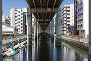 A long expressway overpass bridge above a canal near Asakusa in Tokyo, Japan. Friday July 14th 2017