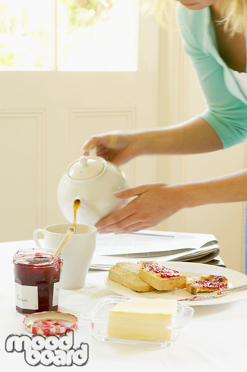 Woman Pouring Tea into cup on dining room table at Breakfast